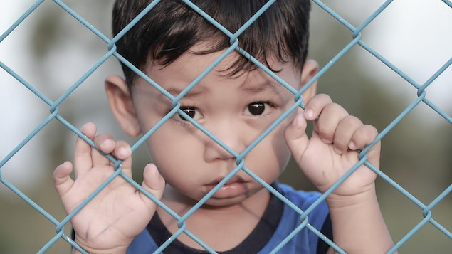 Un enfant derrière une clôture de métal.