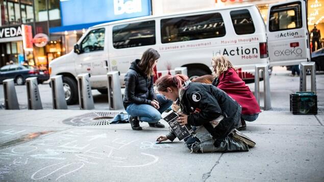 Des jeunes dessinent avec une craie des dessins à même le sol sur la rue Sainte-Catherine à Montréal