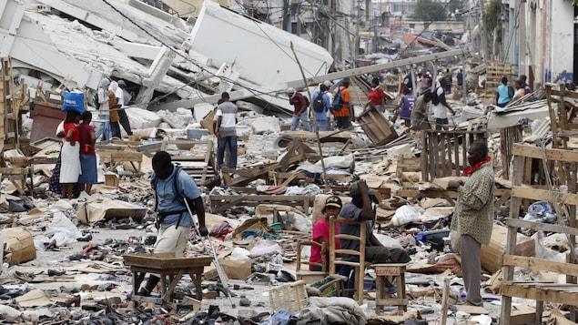 Des résidents marchent dans une rue encombrée de débris de maison à Port-au-Prince après le tremblement de terre de 2010