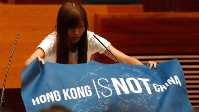 Une jeune femme déploie une bannière où il est écrit, en anglais : « Hong Kong n'est pas la Chine »