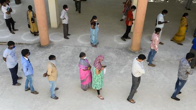 Des personnes attendent en ligne avec distanciation.