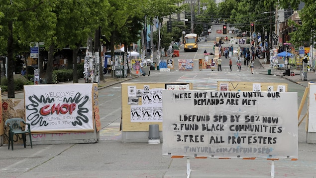 A sign on the street welcomes visitors and a list of demands is posted Wednesday, June 24, 2020, inside the CHOP (Capitol Hill Occupied Protest) zone in Seattle. The area has been occupied since a police station was largely abandoned after clashes with protesters, but Seattle Mayor Jenny Durkan said Monday that the city would move to wind down the protest zone following several nearby shootings and other incidents that have distracted from changes sought peaceful protesters opposing racial ineq