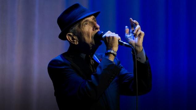 Leonard Cohen chante sur une scène au fond bleu.