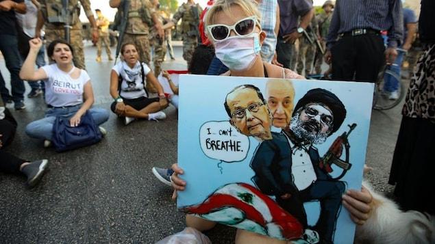 Une manifestante anti-gouvernemental libanais tient une caricature représentant (de gauche à droite), le président du Liban, Michel Aoun, le président du Parlement, Nabih Berri et le chef du mouvement chiite Hezbollah, Hassan Nasrallah, tous assis sur une personne drapée du drapeau national libanais, qui cris « Je ne peux plus respirer ».