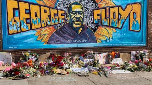 Une murale bleue à l'effigie de George Floyd avec la mention de son nom.