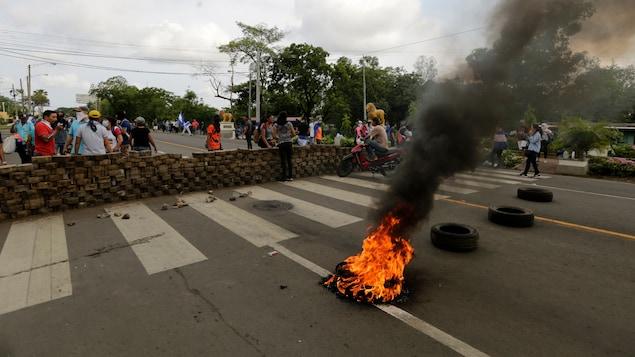 Des manifestants ont érigé une barricade et ont repris les manifestations. Devant la barricade un pneu brûle.
