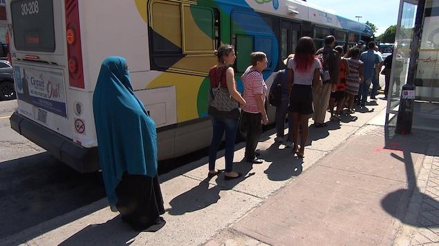 Une femme en niqab fait la file pour monter dans un autobus de la Société de transport de Montréal (STM).