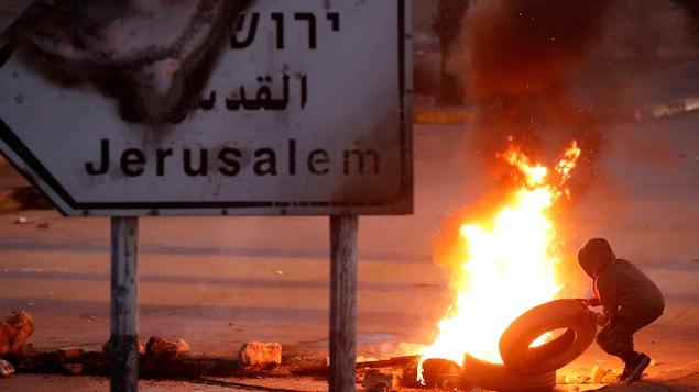 Un manifestant jette un pneu dans une barricade en feu, près de la ville de Ramallah, en Cisjordanie.