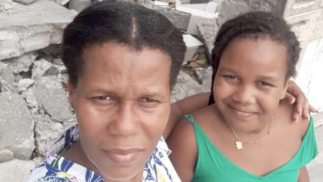 Une mère et sa fille posent devant les ruines de leur maison.