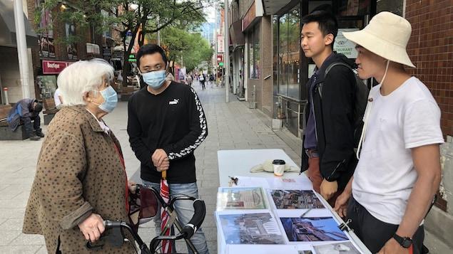 Une femme âgée d'origine chinoise discute avec des jeunes hommes dans une des rues du quartier chinois de Montréal.