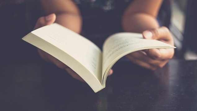 Une personne tien un livre ouvert dans ces mains