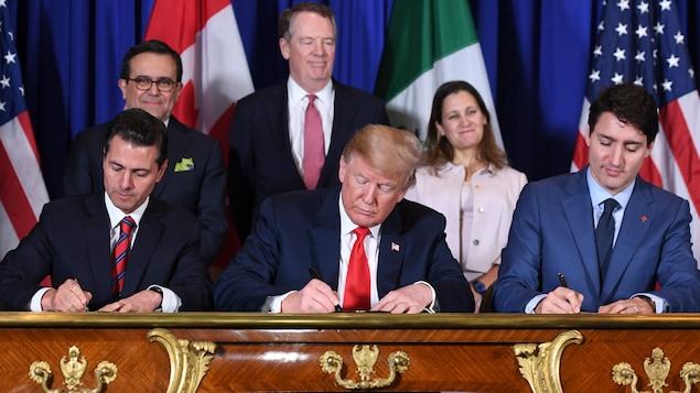 Trois dirigeants politiques sont assis à une table et signent un accord commercial.