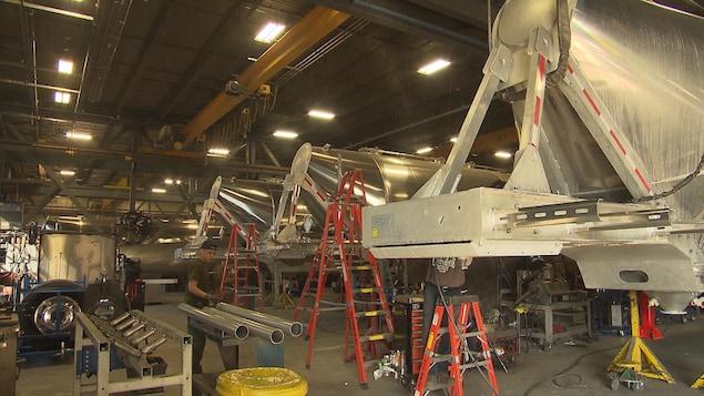 Une usine de fabrication de citernes en aluminium, où on voit des pièces et des ouvriers.