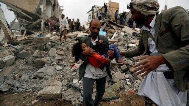 Un homme porte une fillette dans ses bras dans les décombres d'un bâtiment.