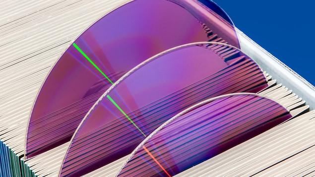 Trois disques CD/DVD violets sortent de leurs pochettes rangées dans un tiroir.