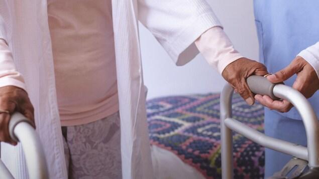 Un préposé aide une femme âgée en marchette.