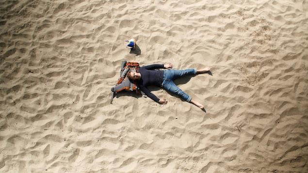 Le réalisateur Julien Robichaud, vu de haut, couché dans le sable sur une plage. Il a la tête appuyée sur son sac de voyage. À coté de lui: une couronne aux couleurs du drapeau de l'Acadie.