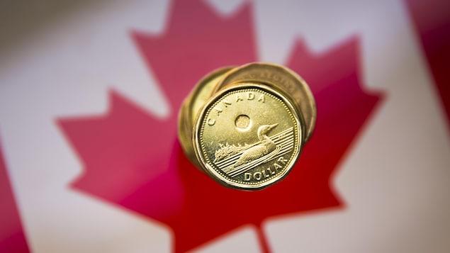 Des dollars canadiens sur un drapeau canadien.