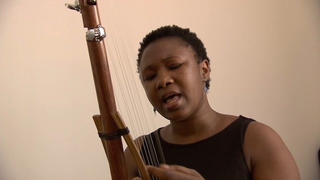 Une femme joue d'un instrument traditionnel en chantant.