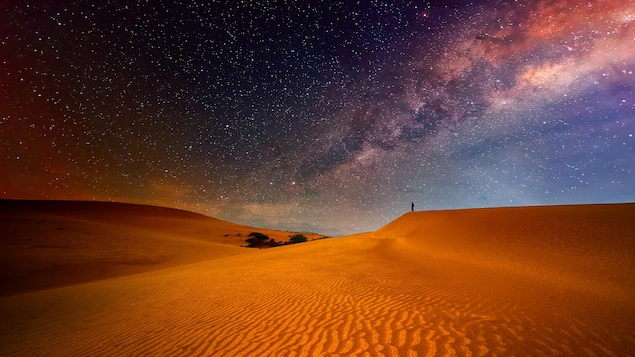Une dune dans le désert sous un ciel étoilé rappelant l'espace.