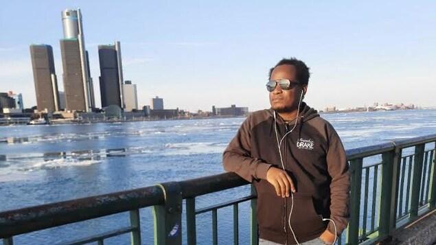 Un homme détendu posant sur un pont devant le centre-ville.