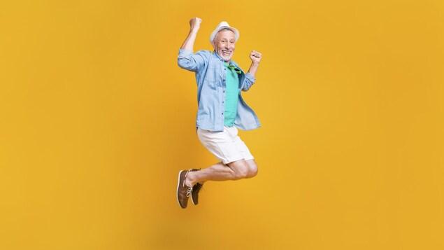 Un homme âgé au style hipster cool saute de joie dans un décor jaune.