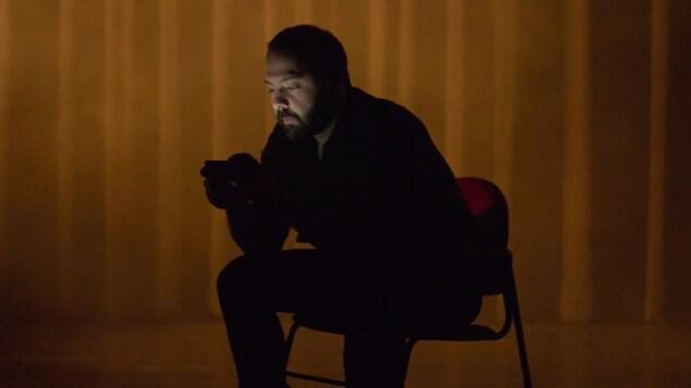 Un homme assis dans la pénombre qui regarde un écran de téléphone cellulaire.