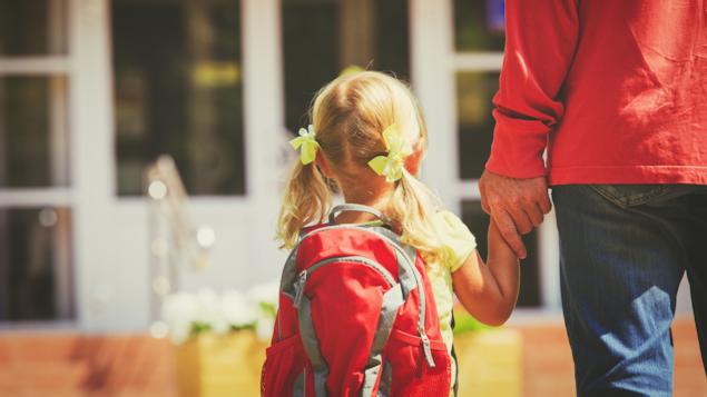 Une fillette accompagnée par son père à l'école.