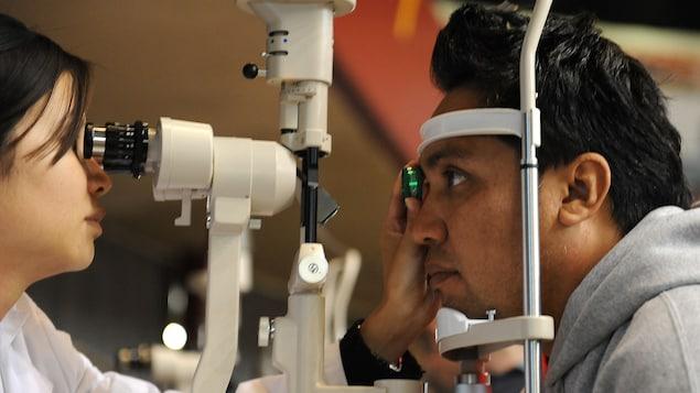 Une optométriste asiatique réalise un examen de la vue sur un homme d'origine latine dont le menton et le front sont appuyés contre un instrument pour stabiliser son visage.