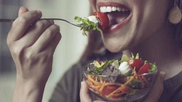 Une femme mange une salade.