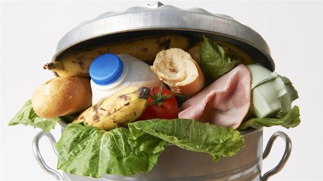 Plusieurs aliments se retrouvent dans une poubelle.