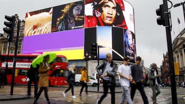 Au centre-ville de Londres, des piétons sont exposés à la publicité plus que jamais.