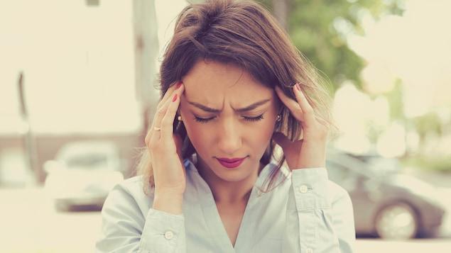 Une femme se bouche les oreilles.