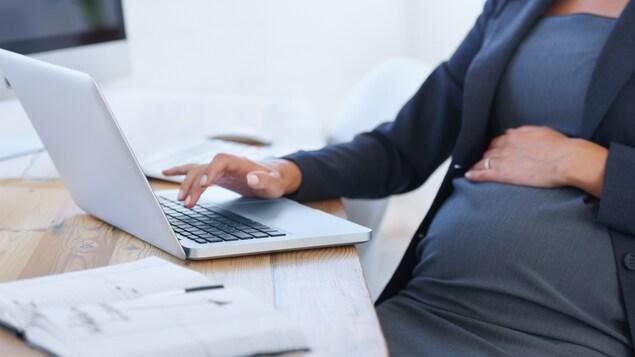 Une femme enceinte est devant son ordinateur au travail.