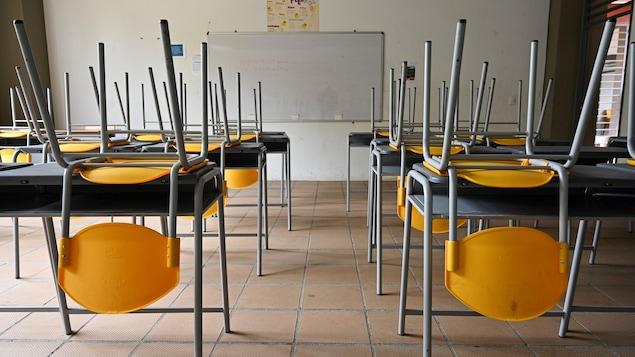Une classe vide; les chaises sont placées sur les pupitres.