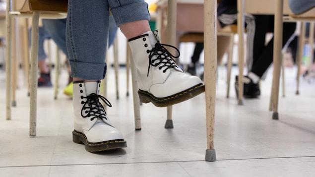 Les bottes d'une élève sous son bureau.