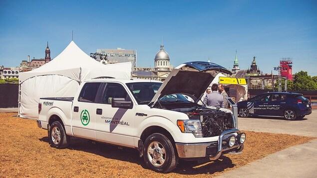 Une camionette blanche en démonstration avec le capot ouvert sous lequel l'on peut voir le moteur électrique.