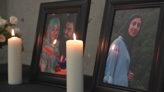 Des bougies devant des photos encadrées.