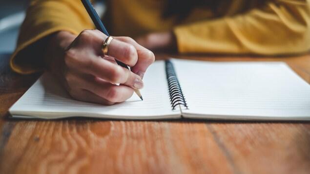 Gros plan sur la main droite d'une femme prenant des notes dans un cahier.