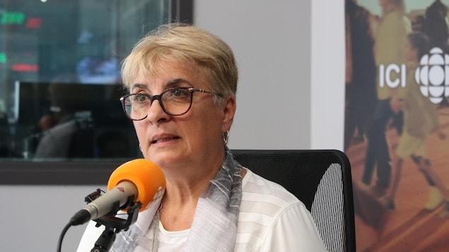 Une femme habillée de blanc parle au micro de l'émission radio C'est encore mieux l'après-midi.
