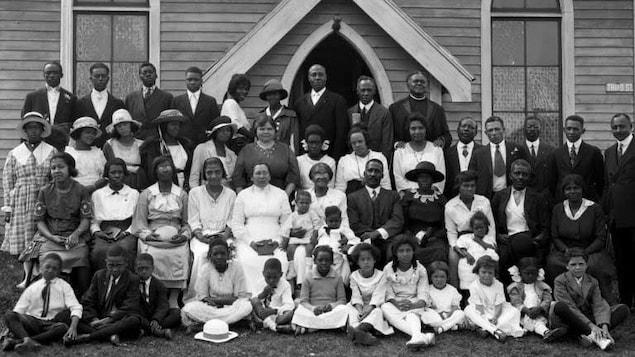Un groupe d'une cinquantaine de personnes rassemblées devant une église.