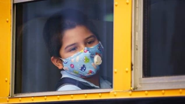 Un élève portant un masque regarde par la fenêtre de l'autobus scolaire dans lequel il est assis.