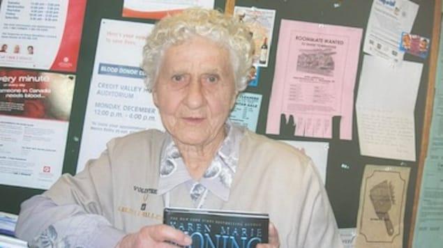 Une femme âgée devant un babillard tient un roman dans ses mains.