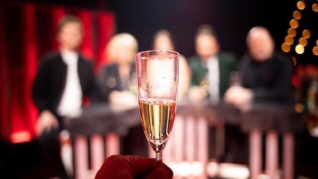 Verre de champagne dressé vers des invités volontairement photographiées en flou.