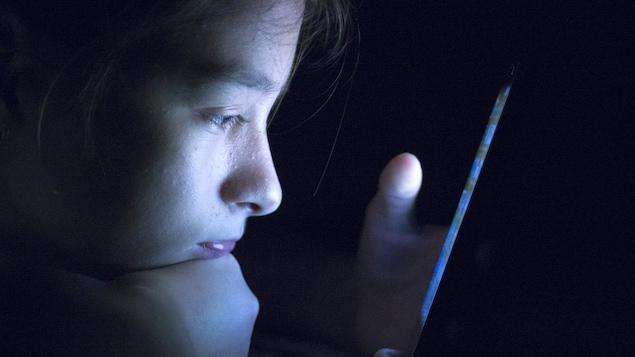 Un adolescent couché sur le ventre et appuyé sur son poing droit regarde l'écran de son téléphone dans le noir.