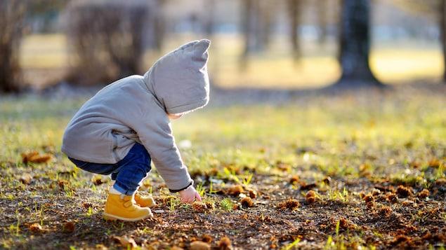 Un bambin est accroupi dans un terrain vert.