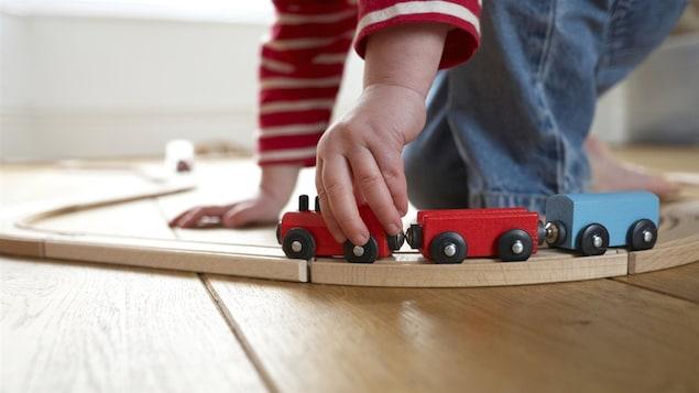 Un enfant joue avec un petit train en bois.