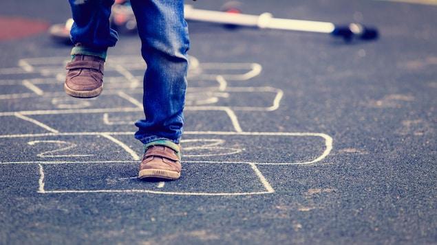 Un enfant joue à la marelle dans la rue.