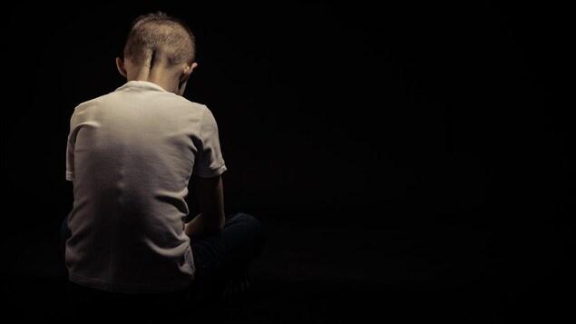 Dans un pièce noire, un enfant de dos la tête baissée.