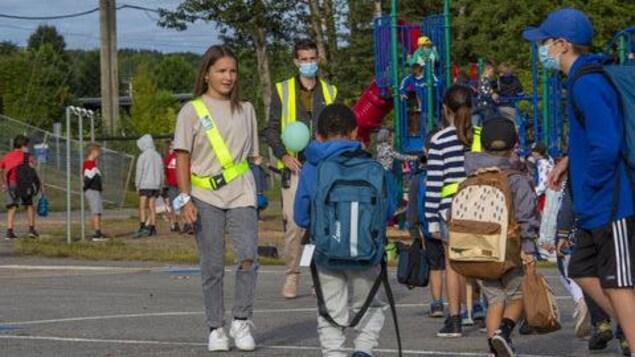 Des brigadiers parlent avec des enfants dans une cour d'école.